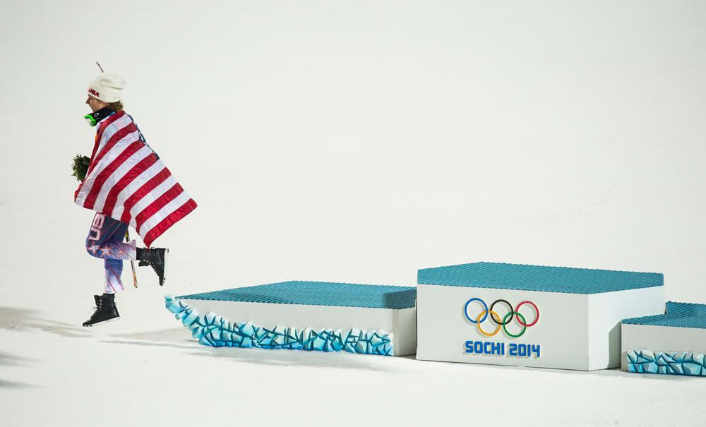 Yhdysvaltain Mikaela Shiffrin hyppää alas palkintopallilta maansa lippuun verhoutuneena.