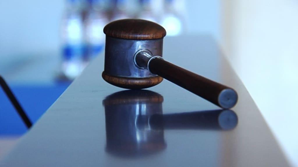 Tuomarin nuija pöydällä oikeussalissa.
