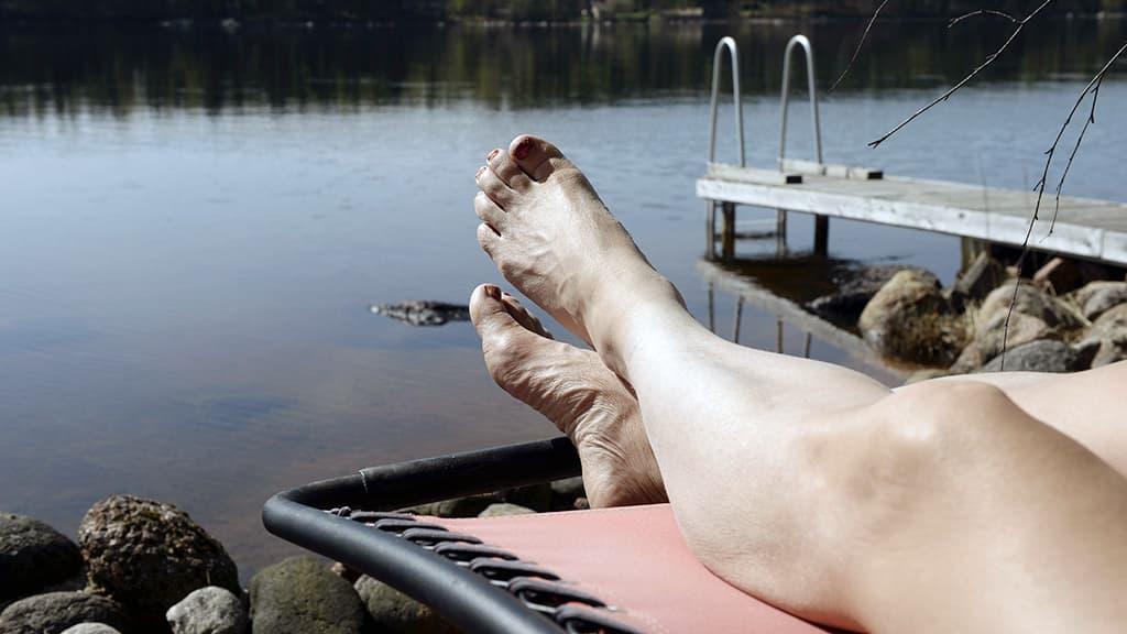 Nainen ottaa aurinkoa järven rannalla.