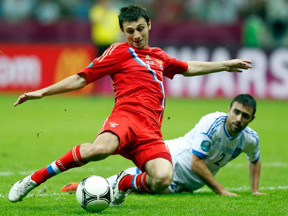 Venäjän Alan Dzagojev kurottaa palloon.