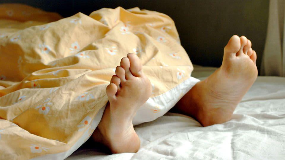 Nukkuvan jalat sängyssä.