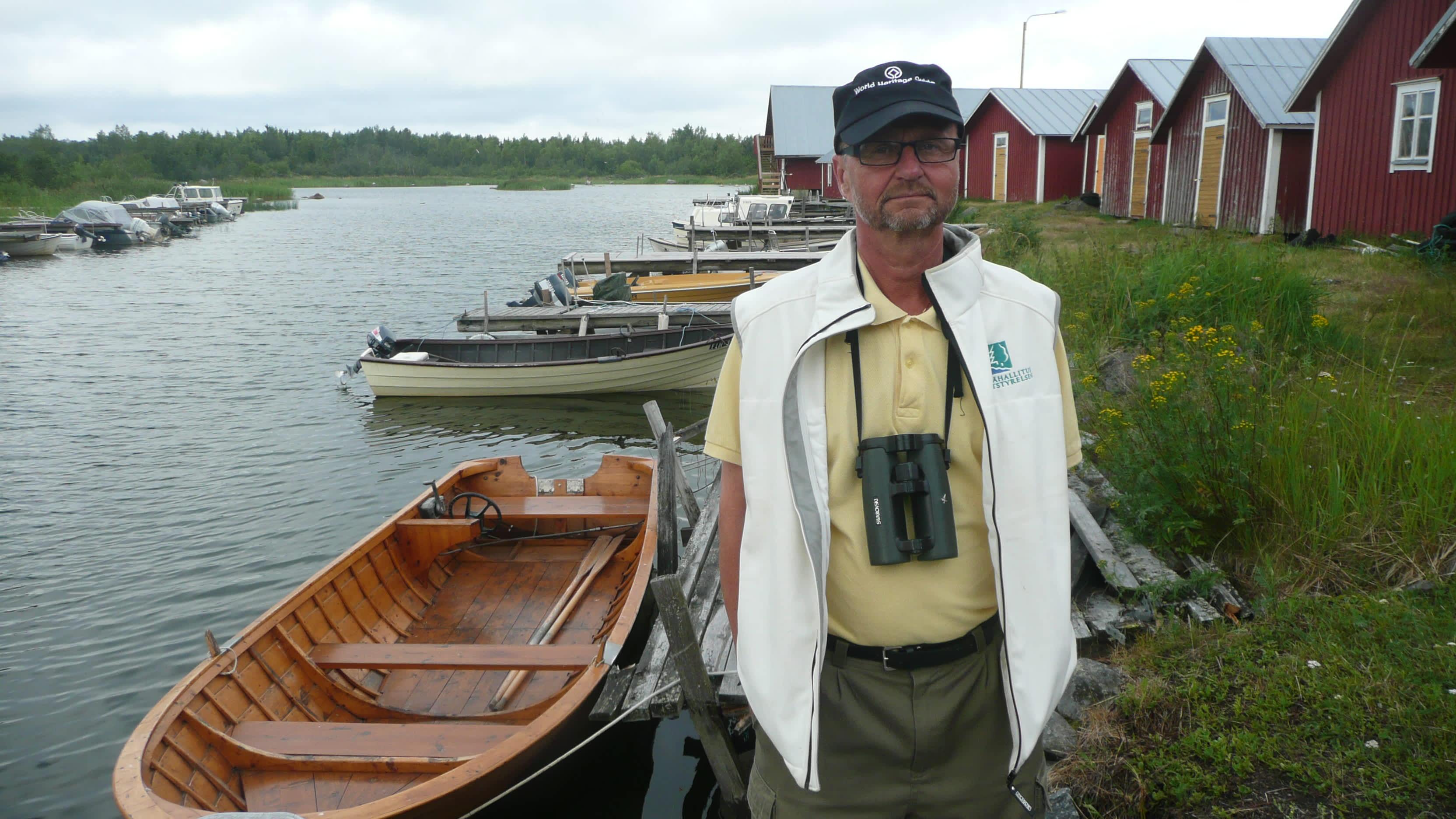 mies edustalla, ja meri, veneitä ja puusatama takana