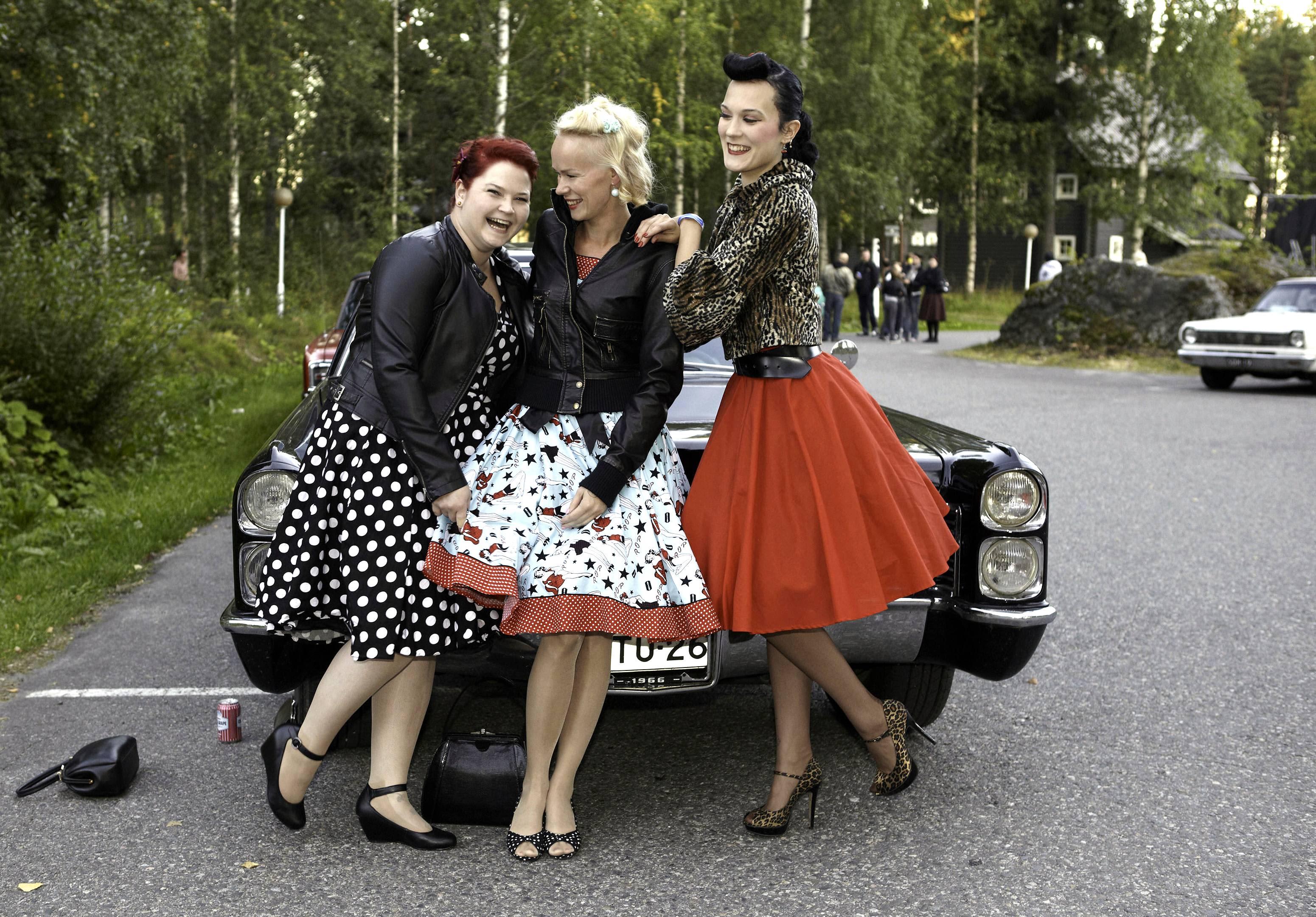Naisia kellohameissa vanhan auton edessä