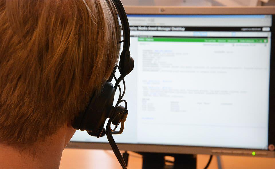 Mies istuu kuulokkeet päässä tietokoneen ruudun äärellä.