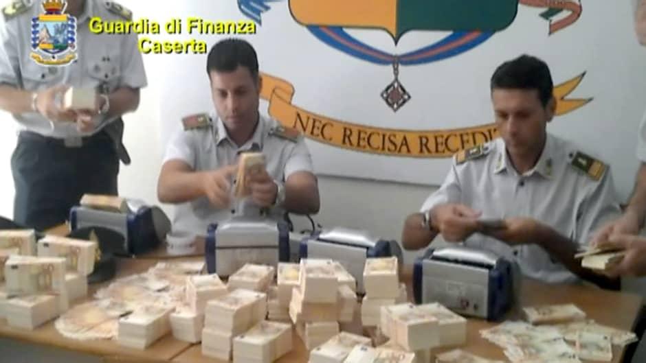 Italialaiset poliisit laskemassa takavarikoituja 50 euron seteleitä.