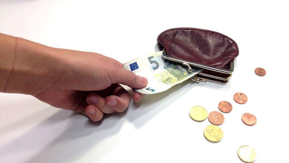 Käsi hamuilee seteliä lompakosta