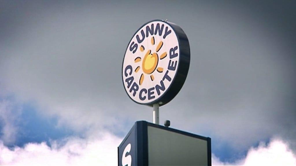 Sunny Car Centerin maston päässä oleva mainoslogokyltti.