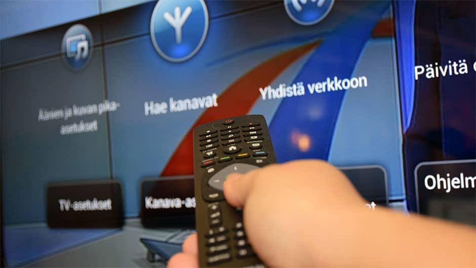Kaukosäädin kädessä osoittaa televisioon