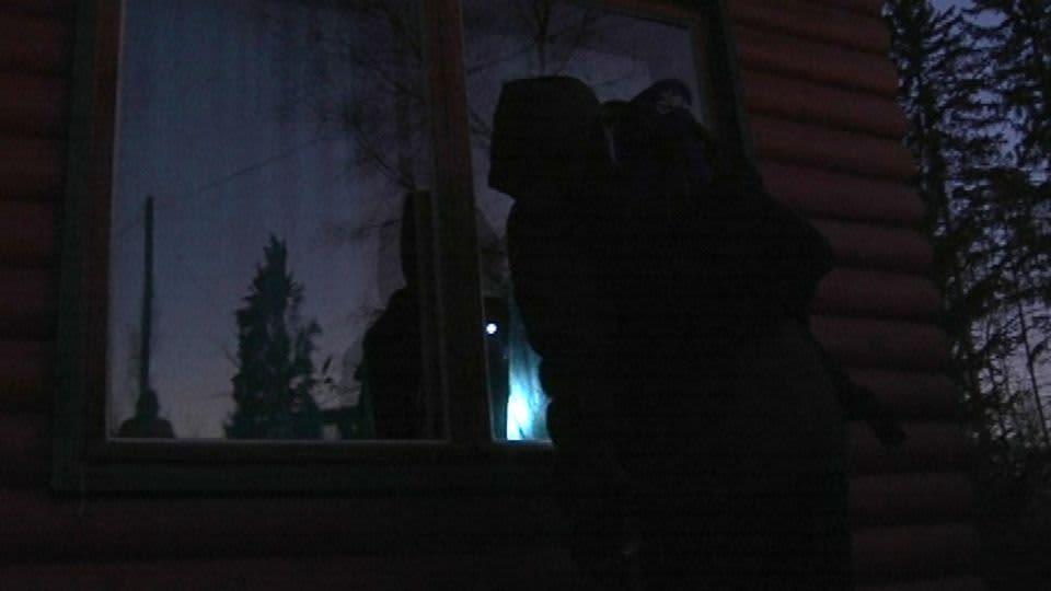 Pimeässä mies kesämökin ikkunan äärellä