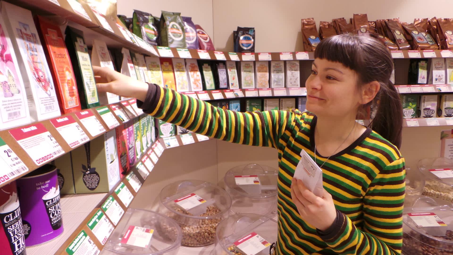 Myyjä laittaa teepakkauksia hyllyyn.