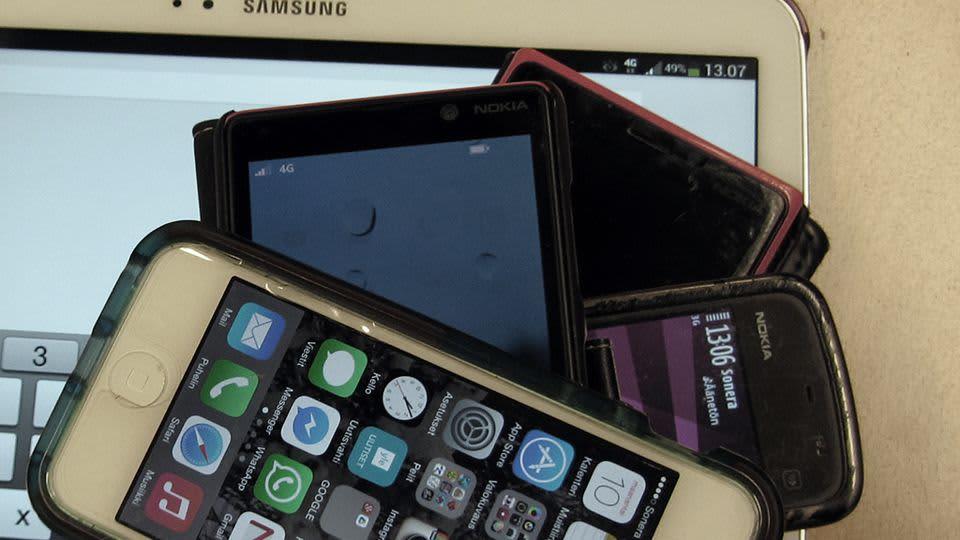 Kuvassa kännyköitä ja tabletti pinossa