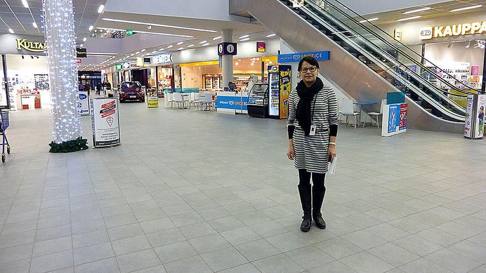 Nainen seisoo kauppakeskuksen aulassa.