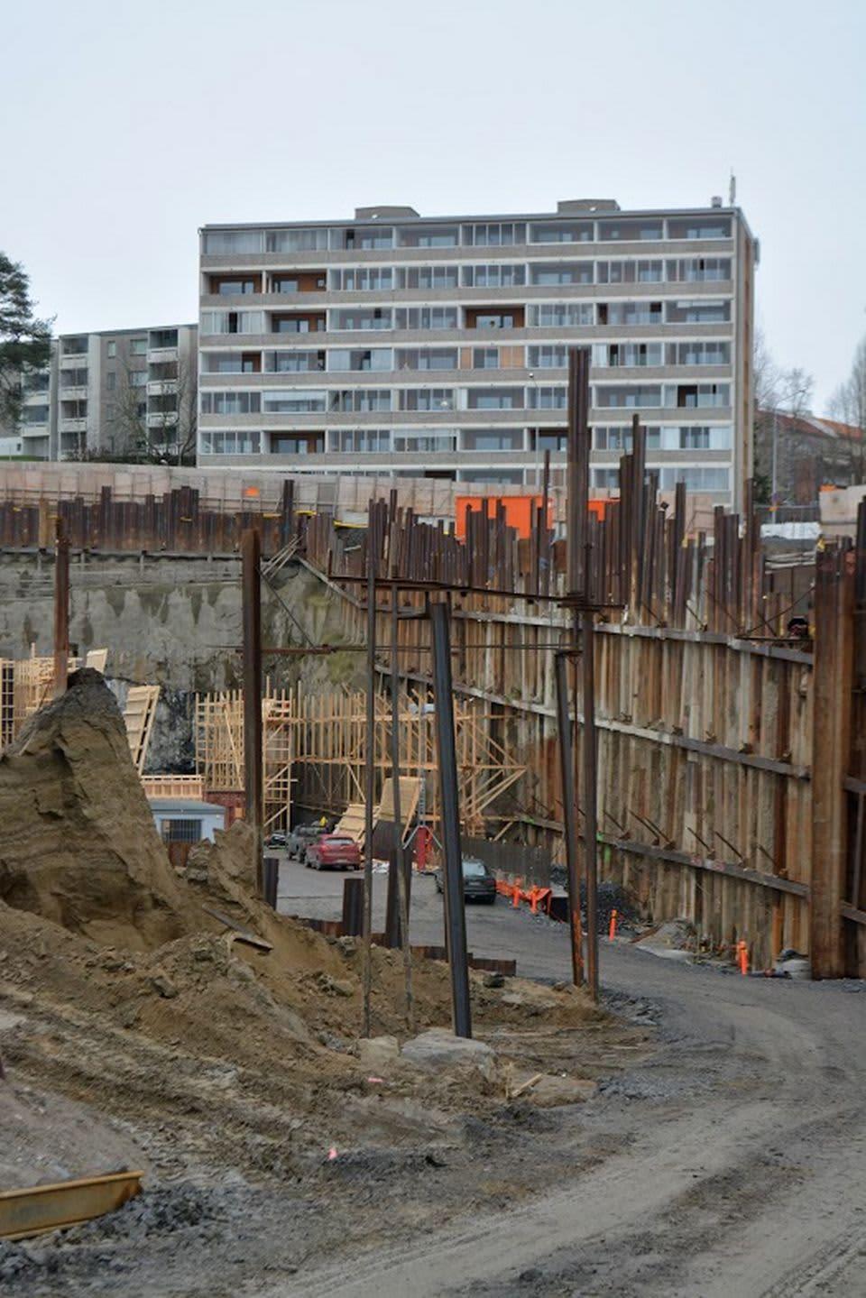 Tunnelin suuaukon massiiviset rakennelmat etualalla, takana kerrostaloja.