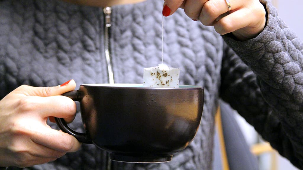 Kuvassa kädessä on teekuppi ja -pussi.