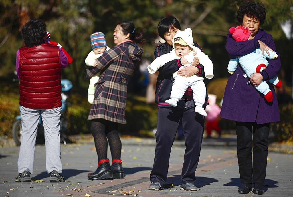 Isovanhempia lapsenlapsen kanssa puistossa.