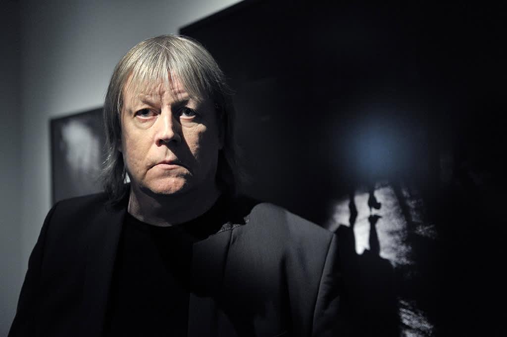 """Valokuvaaja Hannes Heikura teoksensa """"Kamppi 1.10.2010 klo.9.38"""" edustalla Taidehallissa Helsingissä 16. kesäkuuta 2011."""