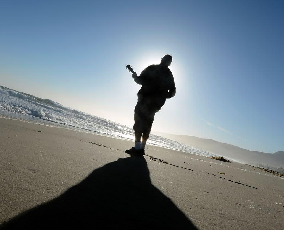 Mies soittaa kitaraa rannalla aurinkoa kohti.