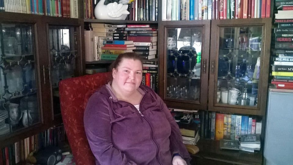 Nainen istuu kirjahyllyn edustalla.
