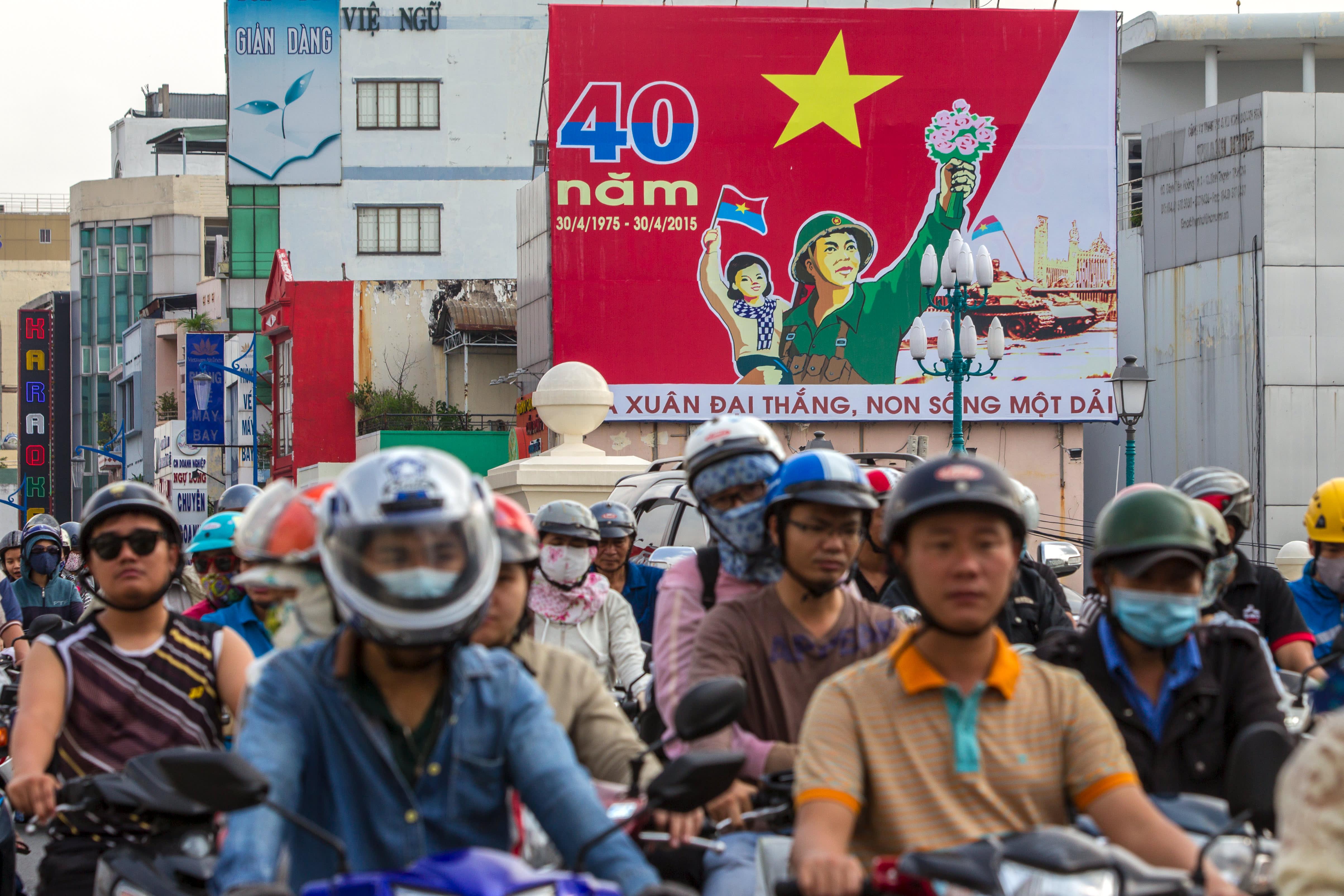 Ihmiset ajavat Vietnamin sodan päättymistä 40-vuotta sitten juhlistavan kyltin ohi Ho Chi Minhissa.