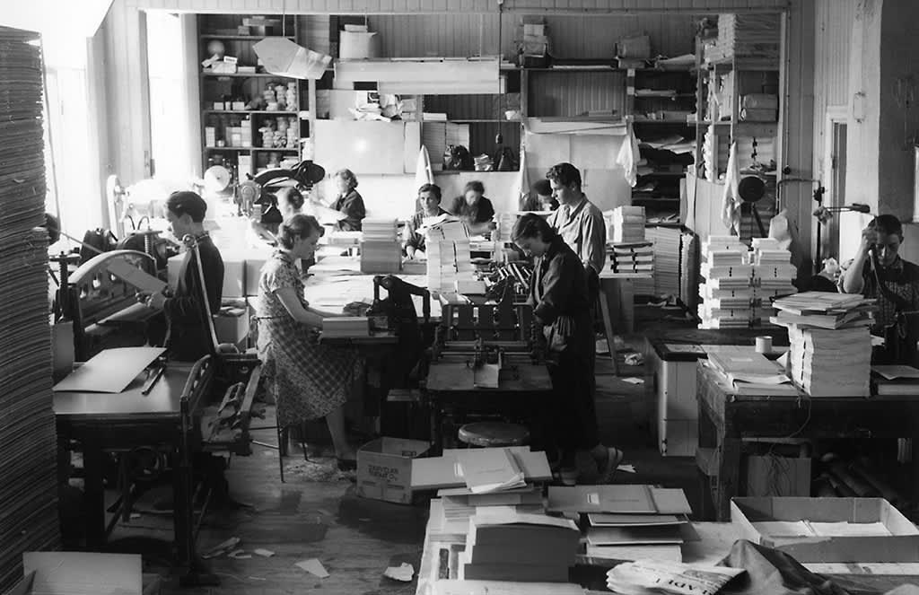 Nuoria miehiä ja naisia töissä porvoolaisessa kirjapainossa.