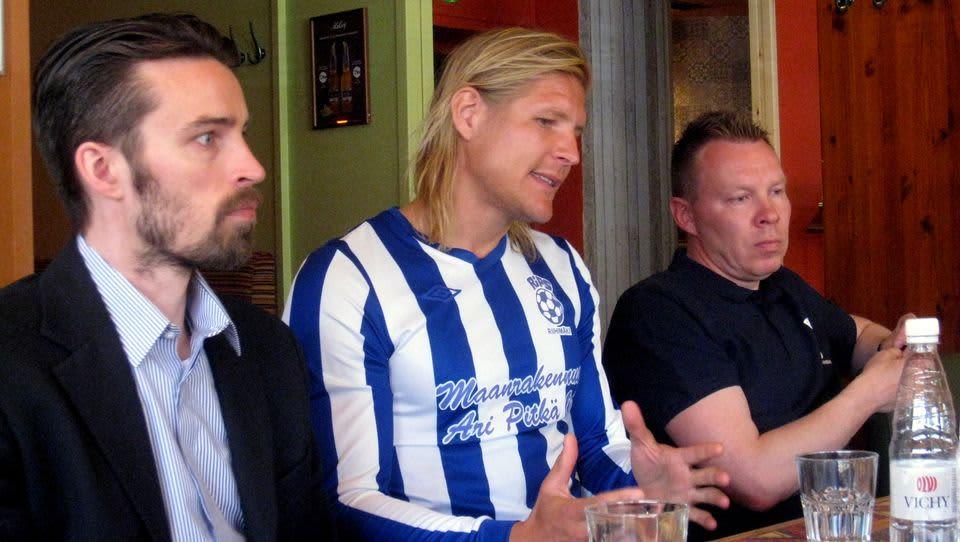 Kolme miestä istumassa pöydän takana vierekkäin