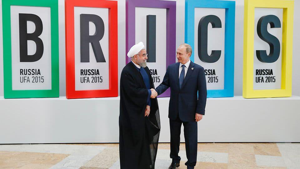 Vladimir Putin ja Hasan Ruhani kättelevät suuren BRICS-tekstin edessä.