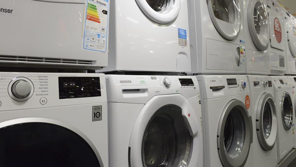 Kuvassa pyykinpesukoneita ja kuivureita rivissä