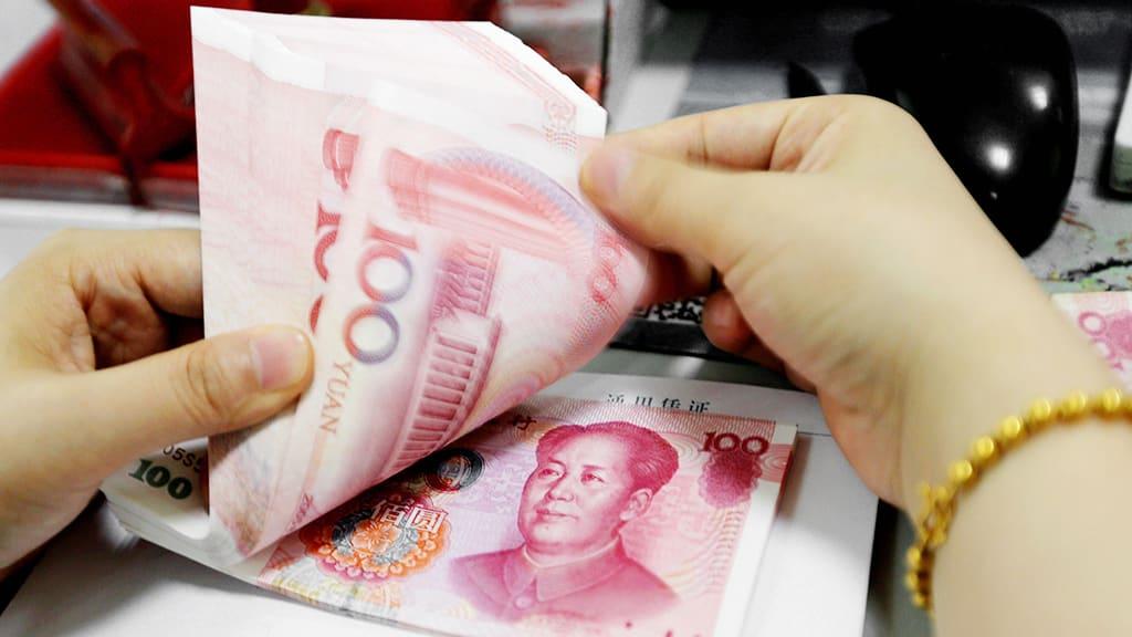 Kiinalainen pankkivirkalija laski rahoja Lianyungangissa.