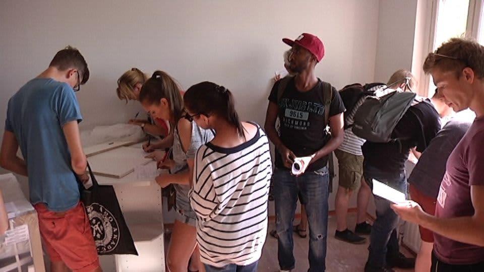 Paljon nuoria opiskelijoita katsomassa vuokralla olevaa asuntoa.