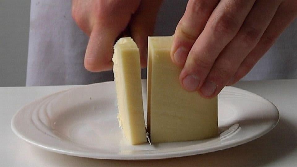 Mies leikkaa juustosta isoa palaa veitsellä