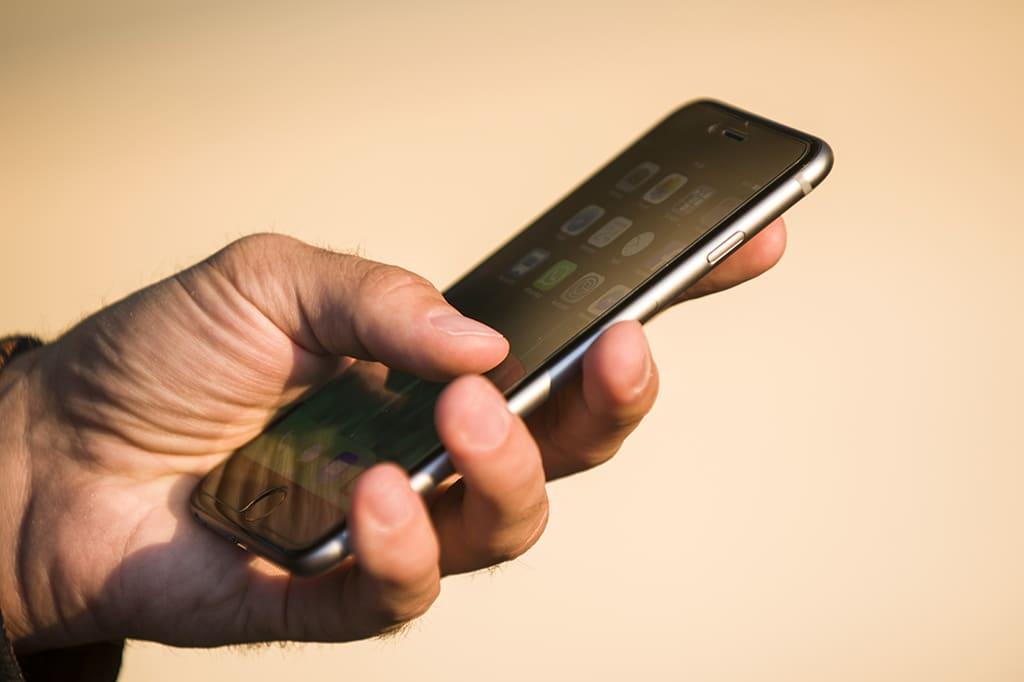 Miehen kädessä iPhone 6 Plus.