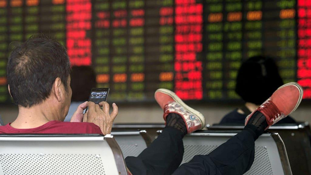 Kiinalainen mies tutkii osakekursseja Shanghaissa.