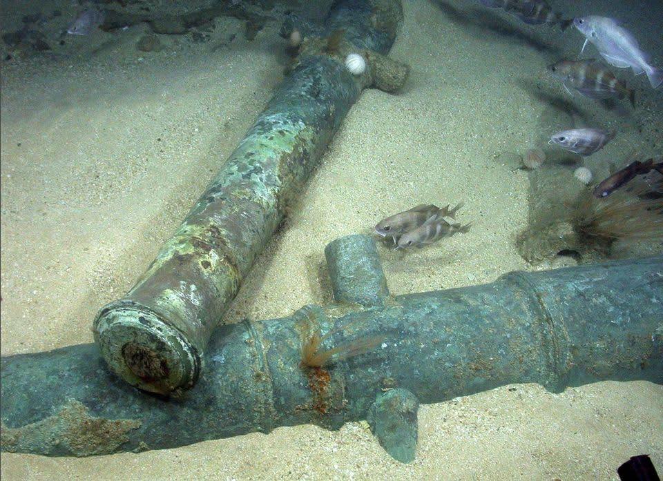 Parvi pieni kaloja uivat meren hiekkapohjassa lojuvien kahden kanuunanputken yllä.
