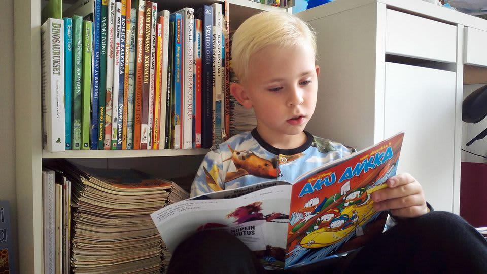 Poika lukee sarjakuvalehteä