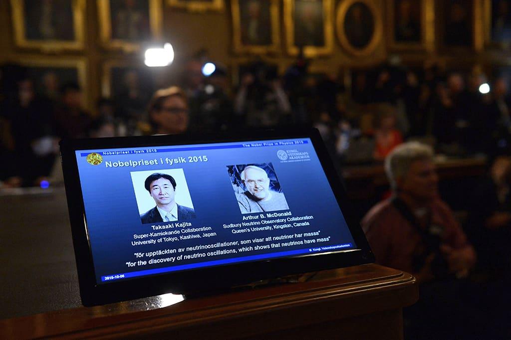 Takaaki Kajitan ja Arthur B. McDonaldin kuvat näytöllä fysiikan Nobel-palkinnon julkistamistilaisuudessa Tukholmassa tiistaina.