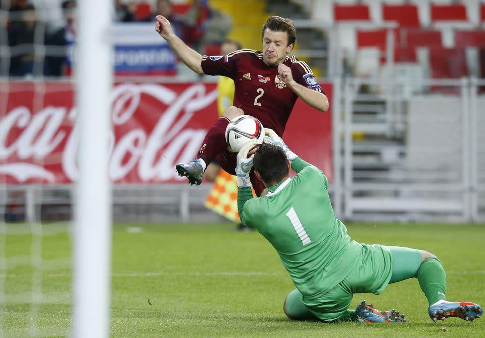 Venäjän Oleg Kuzmin maalinteossa Montenegron maalivahti Milan Mijatoviccia vastaan.