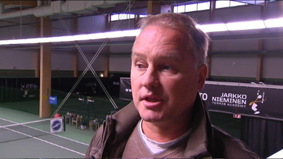 Olli Rahnasto tenniskentän laidalla.