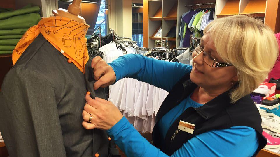 Myymäläpäällikkö Jaana Kallunki näyttää, kuinka kokkivaatteen saamat roiskeet piilotetaan vaihtamalla  miehustan kätisyys.