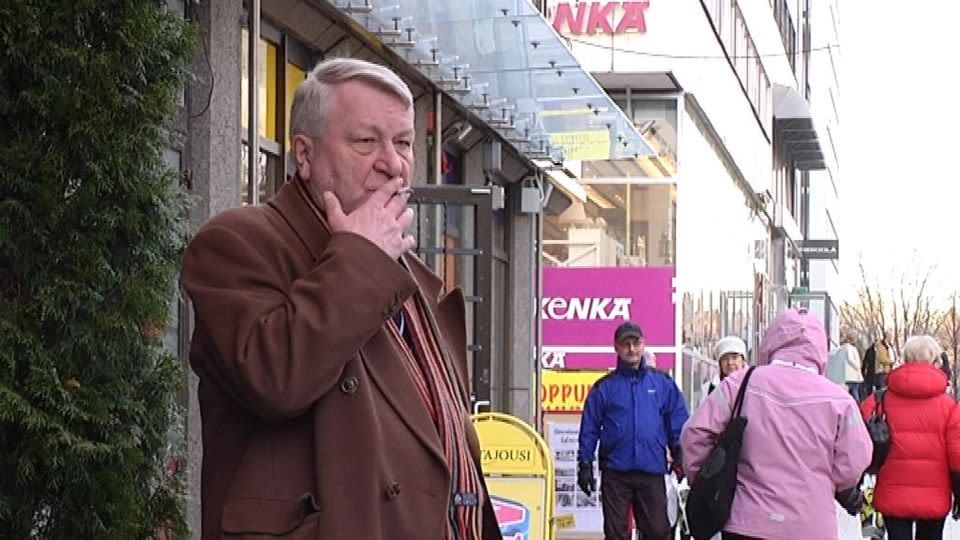 Mies seisoo kadulla ja polttaa tupakkaa.