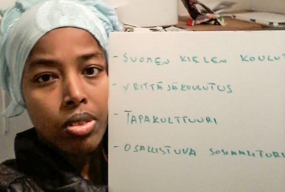 nainen pitelee paperia johon on kirjoittanut