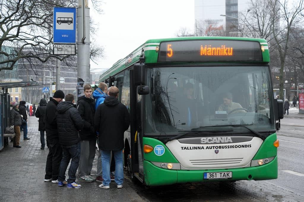 Joukko poikia nousemassa vihreään bussiin sadesäässä Viru-hotellin pysäkillä.