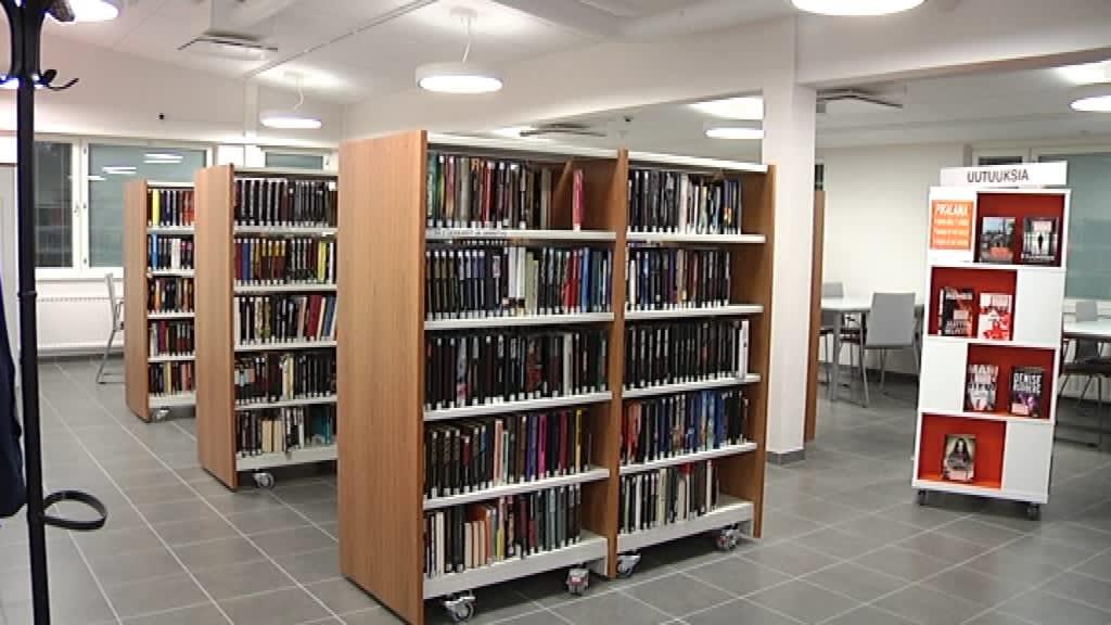 Kirjoja kirjahyllyissä. Seinän vieressä pöytiä ja tuoleja.