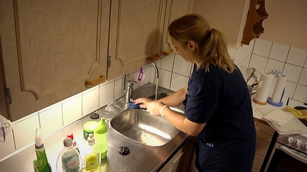 Nainen siivoaa keittiötä