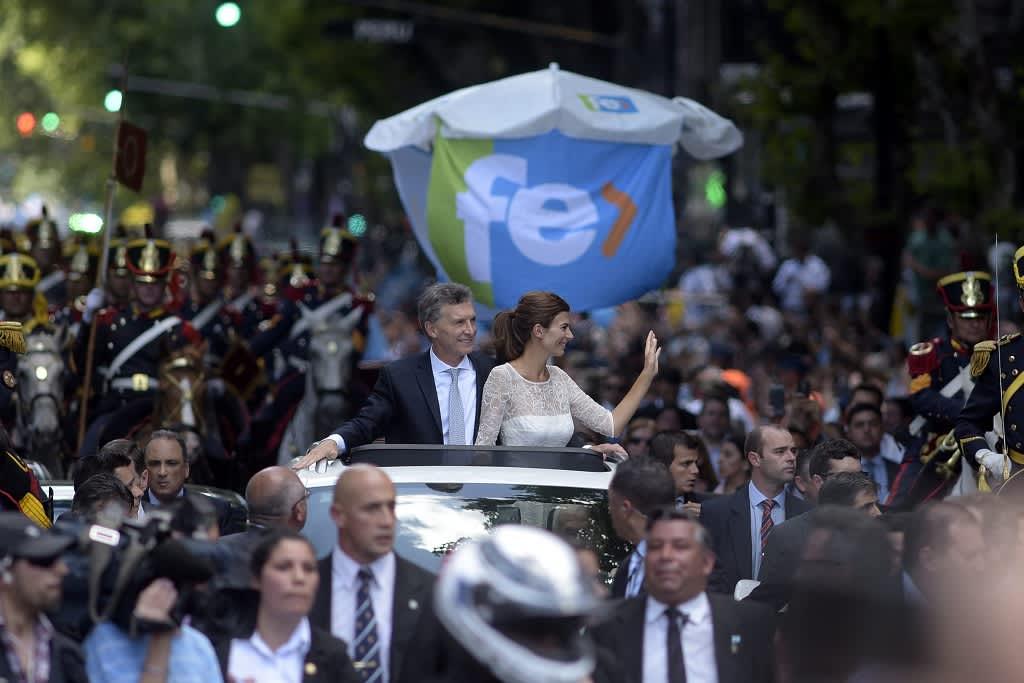 Presidentti Mauricio Macri ja puolisonsa Juliana Awada seisovat autossa, joka kulkee suuren ihmisjoukon keskellä.
