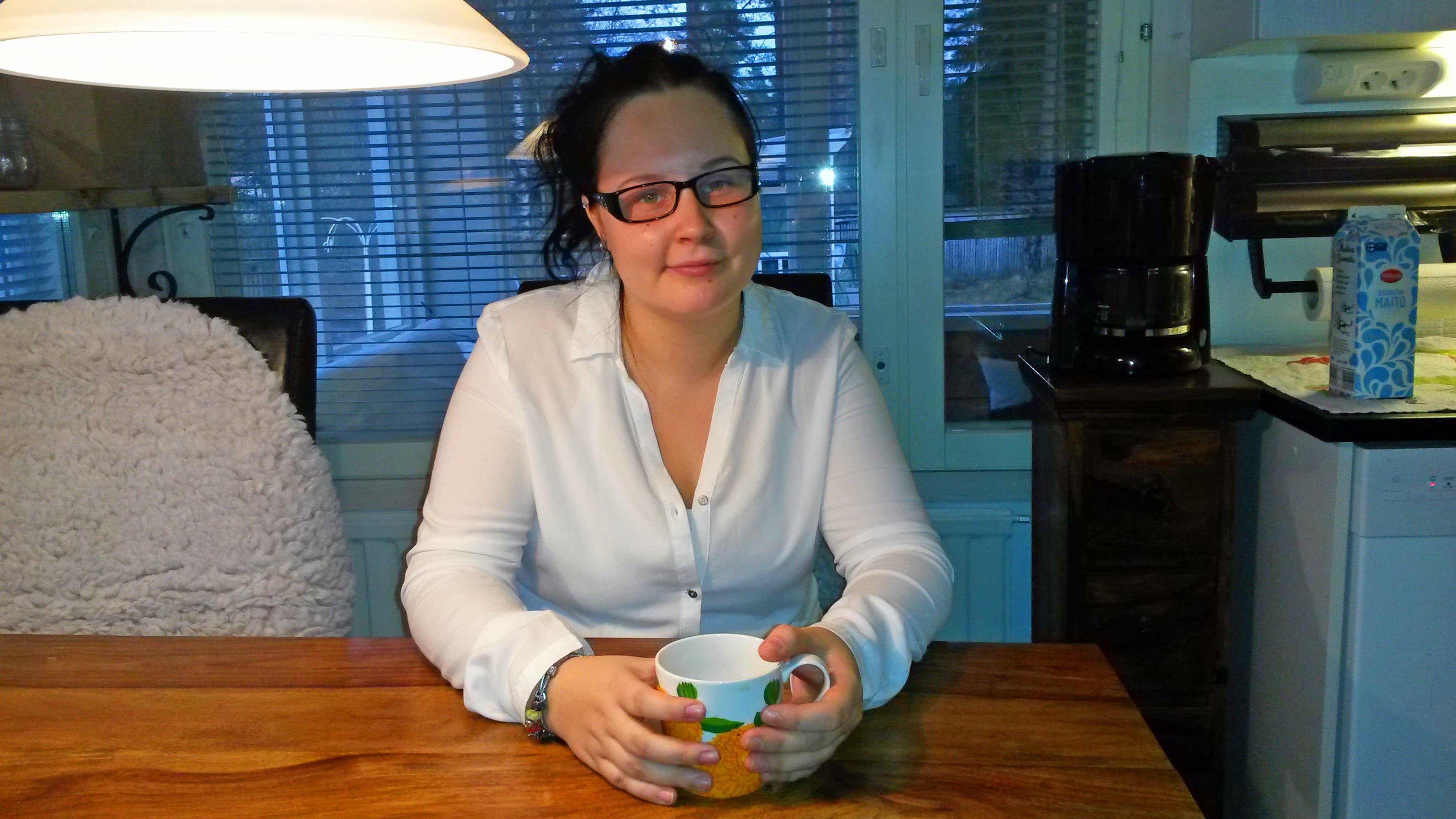 Satu Söderholm istuu kotinsa pöydän ääressä kahvikuppi kädessään