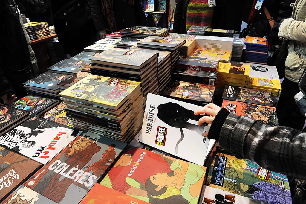 Osallistujat selailevat sarjakuva-albumeita Angoulêmen sarjakuvafestivaaleilla.