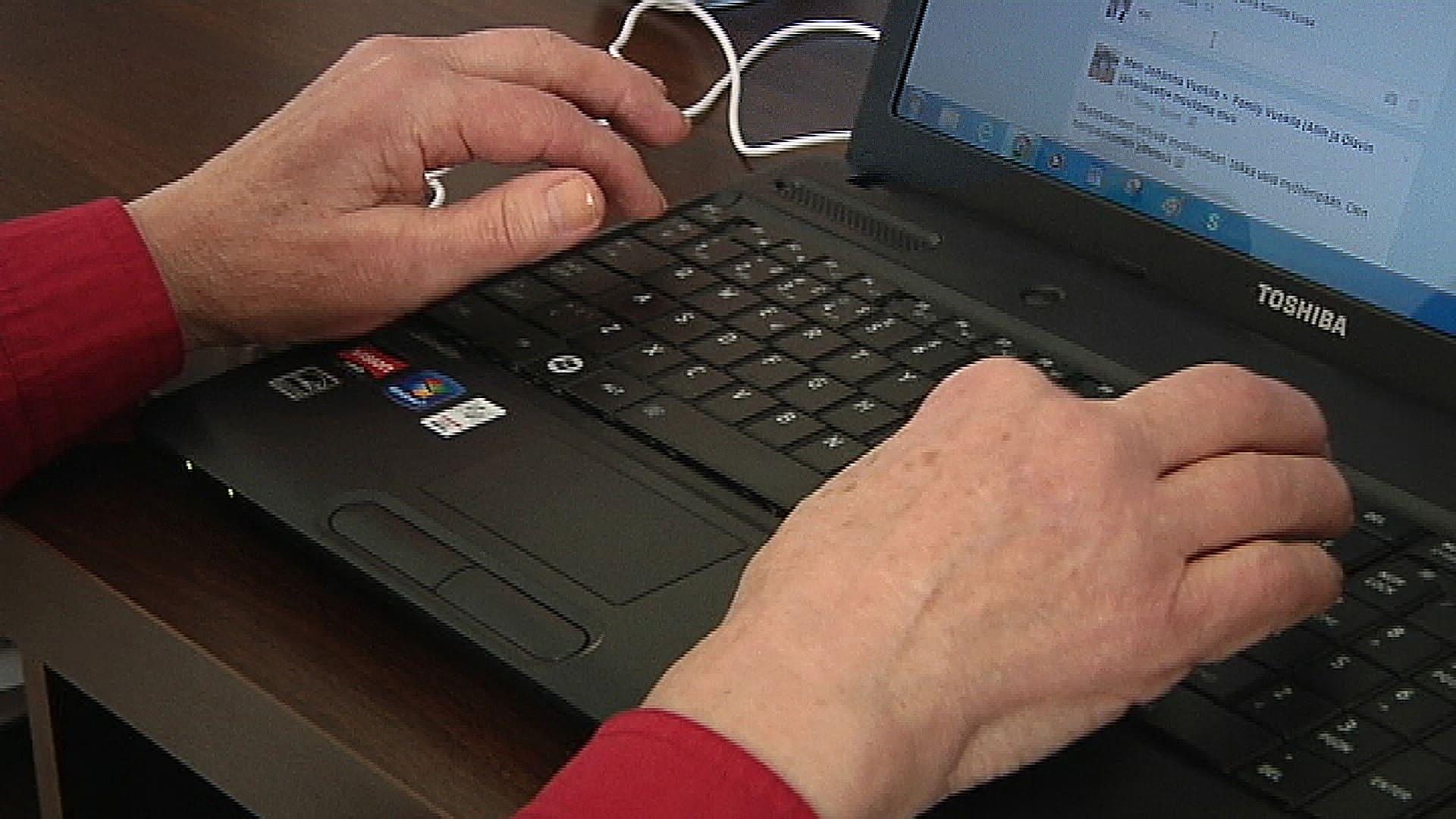 Vanha nainen käyttää tietokonetta.