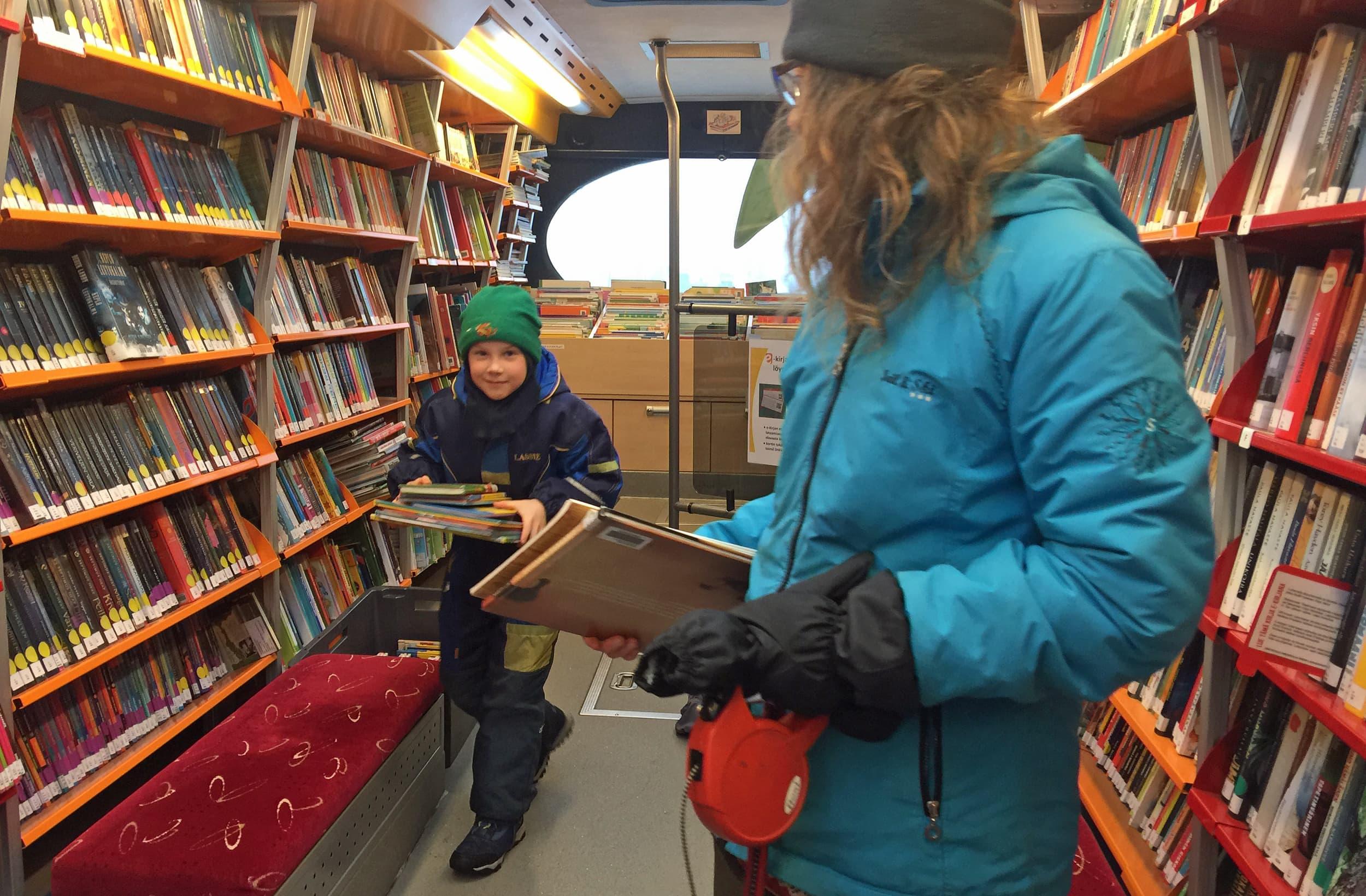 Nainen odottaa kirjastoautossa poikaa, joka tulee kohti kameraa kirjanippu kädessä