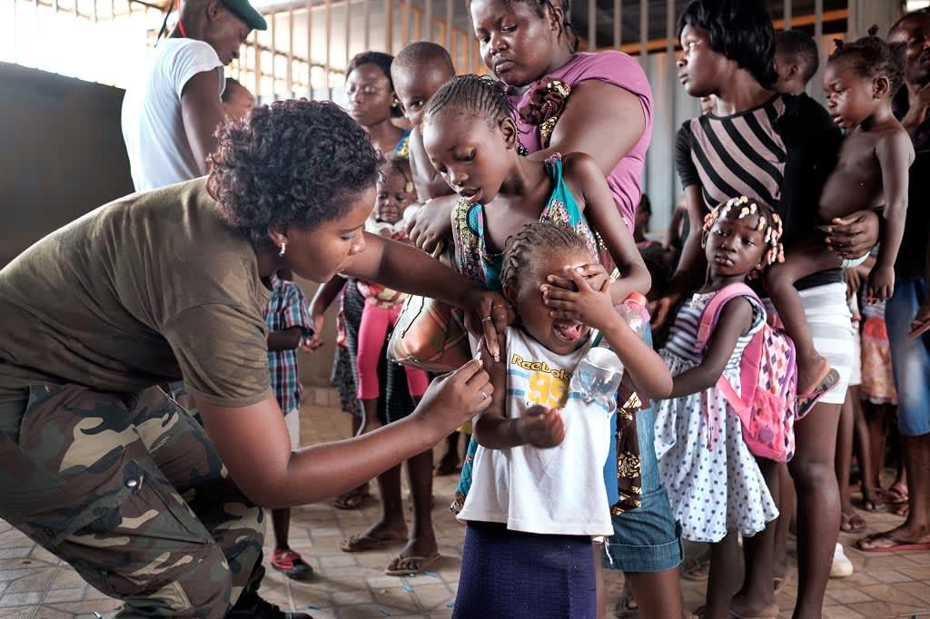 Pikkutyttö peittää silmänsä, kun naissotilas pistää rokotuksen hänen käsivarteensa. Jonossa on muita lapsia ja heidän äitejään.