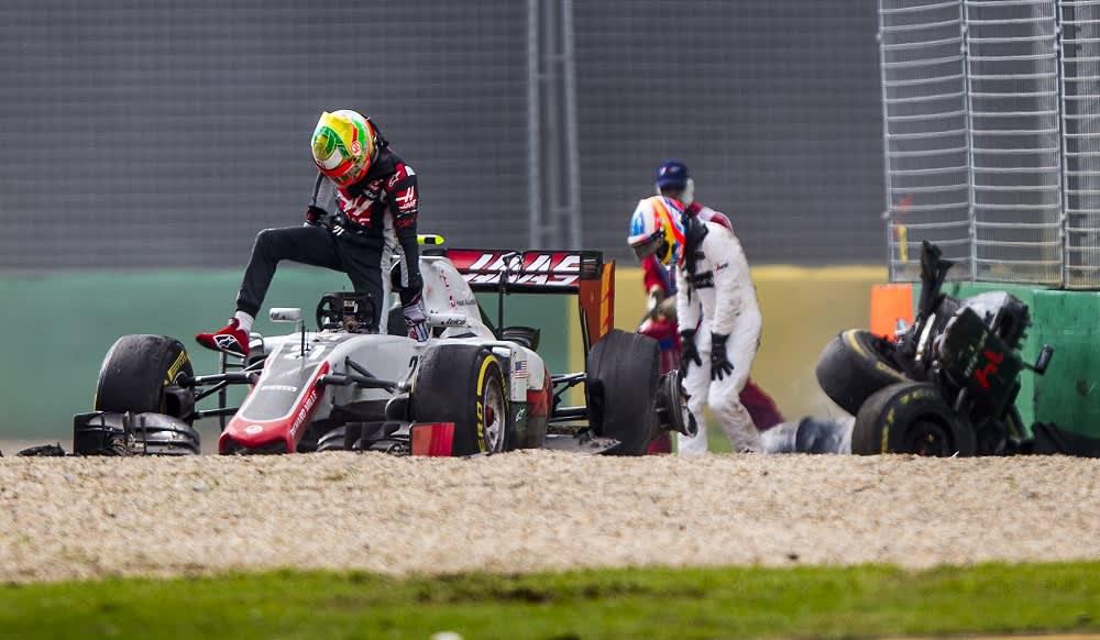 Haasin Esteban Gutierrez nousee autosta, McLarenin Fernando Alonso nojaa polviinsa ulosajon jälkeen.